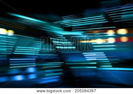 Blue and turquoise lights of urban city surrounding moving and blurred by motion