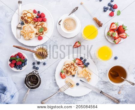 Flat lay with breakfast with scotch pancakes in flower form, berries and honey on light wooden table. Healthy food concept with copy space.