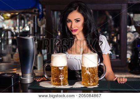 Sexy woman in dirndl dress holding Oktoberfest beer stein at the pub.