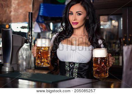 Sexy woman in dirndl dress holding Oktoberfest beer stein at the pub. Oktoberfest