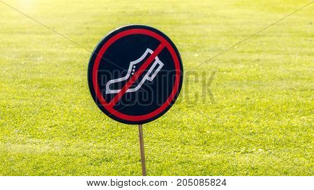 No walking on the grass sign (backlit).
