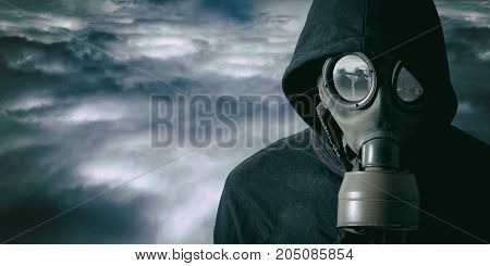 Portrait of a man with a gas mask in a dramatic of cloudy background. There is a contaminant factory in the reflection of the glasses