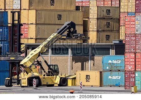 ANTWERP BELGIUM - JUL 9 2013: Mobile container handler in action at a container terminal in the Port of Antwerp.