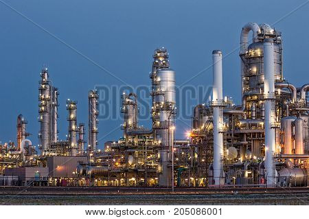 Pipe work of an oil refinery plant after sunset