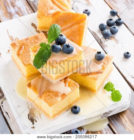 Traditional homemade baked pudding cake with custard cream and blueberries. Healthy dessert.