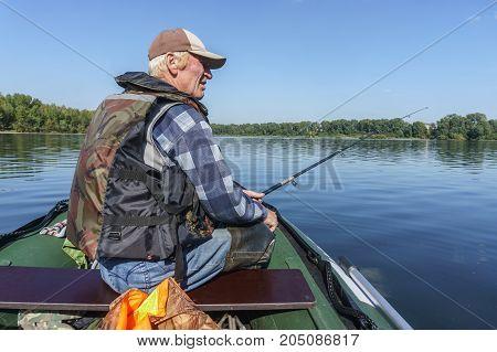 fisherman sitting in the boat fishing spinning