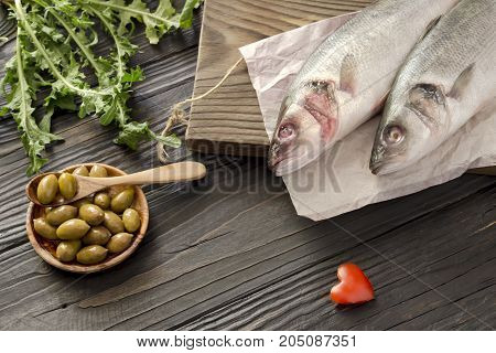 Two raw european bass (Dicentrarchus labrax) on a wooden table closeup
