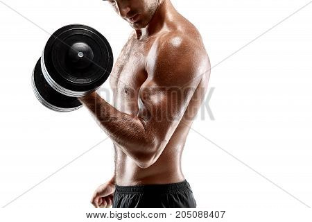 Handsome muscular man with bare chest lifting dumbbell. Dressed in a black sports shorts. Posing on white studio background