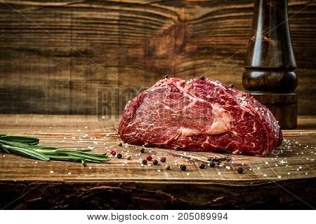 Dry aged Ribeye Steak with seasoning on wooden background. Still life. Copy space. Close-up