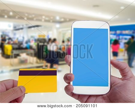 Smart phone online shopping and credit card Shopping center in background.