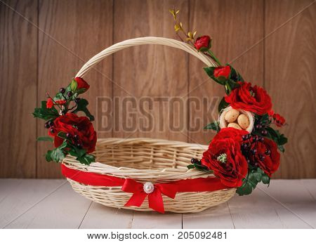 Beautiful decorative basket with flowers to celebrate Easter on a wooden background