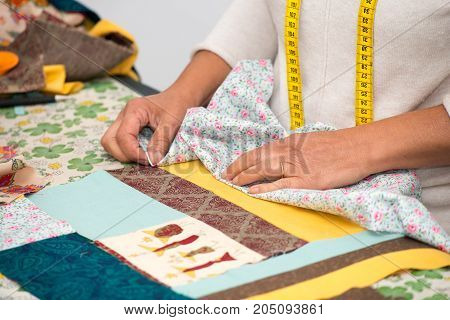 a close up of woman's hand sewing patchwork