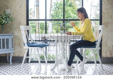 Asian woman is enjoying with coffee break and using cell phone at coffee shop.