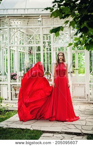 Beautiful Woman in Red Evening Gown in Spring Garden Outdoors