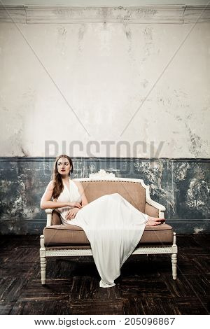Beautiful Fashion Model Woman in White Dress on Vintage Sofa on Retro Background