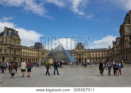 Paris France - July 23 2011: Tourists walk in front of the Louvre museum