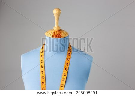 Blue tailor dummy with measuring tape alongside the wall