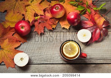 Warming cup of tea, decor of autumn leaves, apples on wooden board. Fall still life, vintage style. Top view.