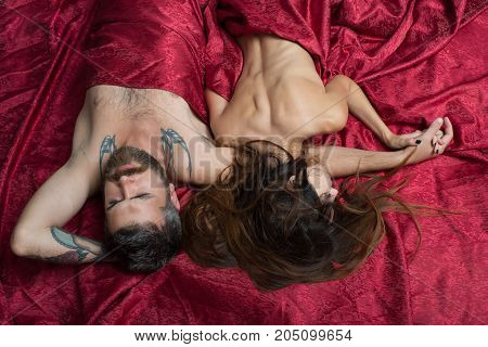 Guy with beard and lady with half covered bodies. Couple in love lies on burgundy sheets. Love and sex concept. Bearded man lying on back with pretty lady on shoulder.