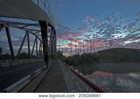 Bridge Over River At Sunset With The Crimson Clouds