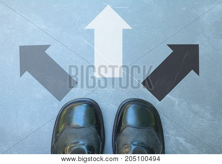 Top view of man wearing black shoes choosing a way marked with black and white arrows. Chooses the right path concept.
