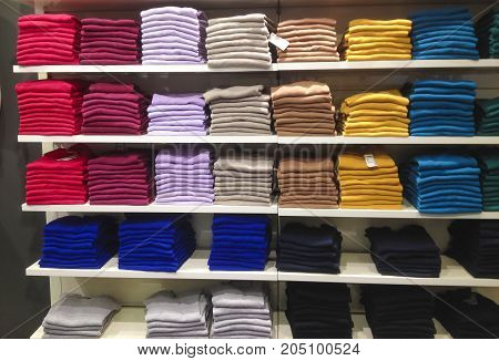 Rows of folded colorful clothes in a shop