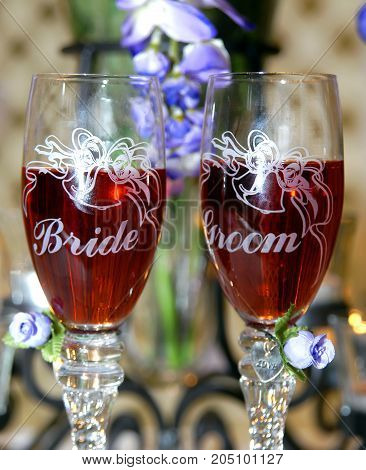 His and her champaigne glasses sit side by side at wedding reception venue. One has