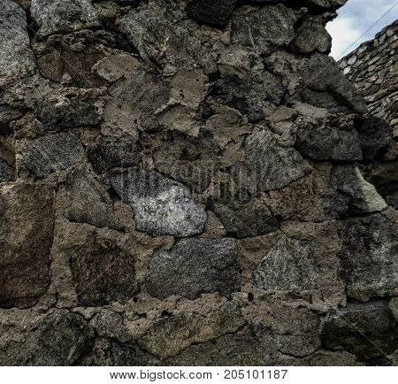 Stone wall. Fragment of ruined stone walls. Stone background. Stone texture. Fortress wall.