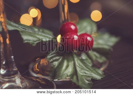 Detail of two champagne glasses placed on the table with mistletoe and Christmas tree and lights in the background. Selective focus