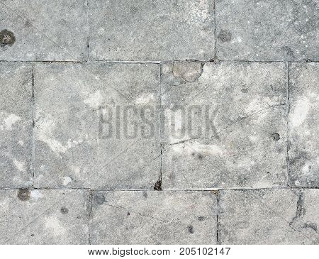 Stone floor tiles with the crack in the pathway of the historical park.