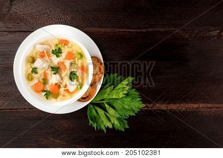 An overhead photo of a plate of chicken, vegetables, and noodles soup, shot from above on a dark rustic texture with slices of bread, a celery branch, and a place for text
