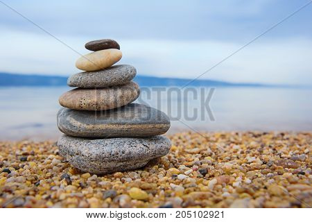 beautiful pyramid of colorful pebbles . Rock Zen in the background of the sea. Concept of harmony and balance.