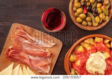 Overhead photo of traditional Spanish tapas. Pickled olives, patatas bravas, potatoes with red and white sauce, jamon, and cheese, with a glass of red wine, shot from above on a dark rustic texture
