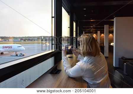 Kloten Switzerland - May 30 2017: Zurich airport departure area interior. Woman passenger taking pictures of the plane on the smartphone. Zurich Kloten Airport is the largest international airport of Switzerland