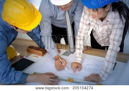 Engineering team is meeting, planning construction work, looking paper plans at construction site