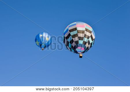 Pair of colorful hot air balloons set against a clear blue sky. Seen from below.