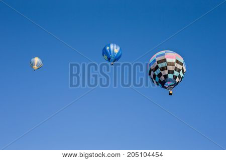 Three colorful hot air balloons set against a clear blue sky. Seen from below. Room for copy in the sky.