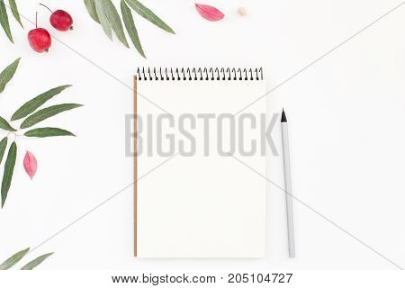 Workplace with notepad pencil and flowers on white. Top view summer romantic pattern