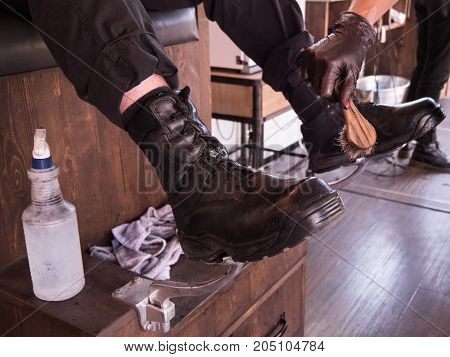man getting his black work boots shined