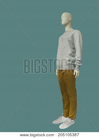 Full-length male mannequin dressed in sweater and trousers isolated on green background. No brand names or copyright objects.
