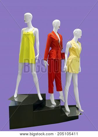 Three female mannequins dressed in fashionable clothes isolated. No brand names or copyright objects.