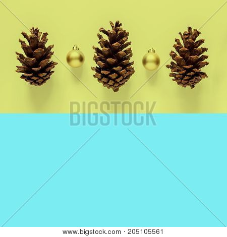 Christmas holidays minimal background. Fir and golden ball on yellow and blue background. Top view with copy space.