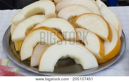Melon or a piece of sliced melon slices. Yellow melon on a tray.