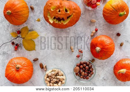 Carved smiling halloween pumpkin head among pumpkins on grey background top view.