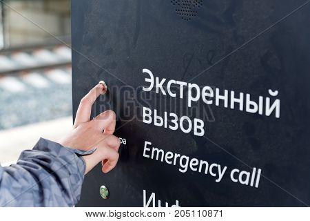 the boys hand presses the emergency call button at the station