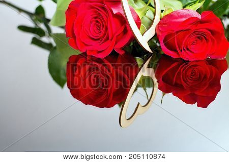Red roses with heart with reflection in mirror. For lovers. Roses heart leaves and mirror. Romantic atmosphere.