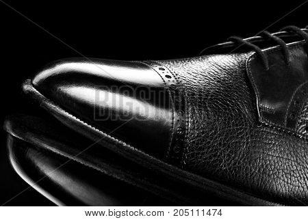 Black oxford polished shoes on black miror background.Shoes shine. Close up.