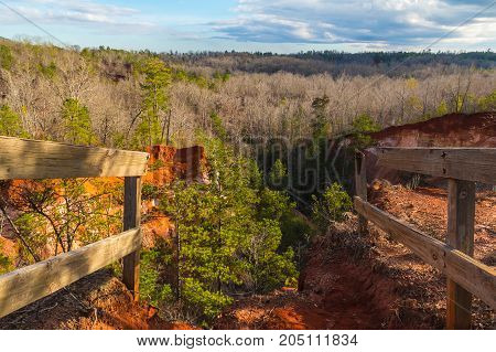 Aerial view of canyons and thicket in the Providence Canyon State Park in sunny autumn day with fences in the foreground Georgia USA