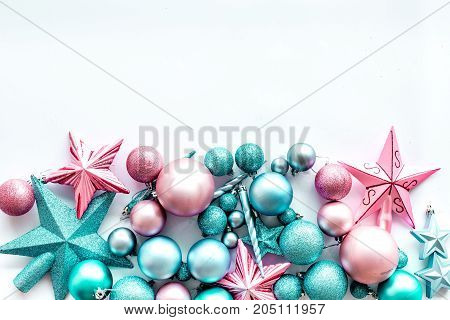 Christmas decoration pattern. Pink and blue stars and balls near pine branches on white background top view.