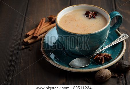 Indian masala chai tea. Spiced tea with milk on dark  wooden background, selective focus.